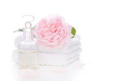 Rose oil with towels - isolated on white. Rose oil isolated on white with pink rose - spa arrangement royalty free stock photo