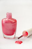 Rose opened nail varnish with spilled on a white background Royalty Free Stock Photos