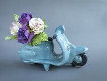 Rose paper flower on ceramic blue scooter. Flower delivery service concept Stock Photo