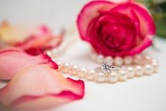 Rose, pearl and diamond ring. Rose, rose petal, pearl and diamond ring Royalty Free Stock Photography