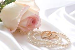 Rose, Perlen und wedrings über weißem Satin Lizenzfreie Stockfotos