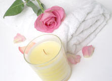 Rose Petal Spa. Pretty pink rose with scatter petals on a crisp white towel and scented vanilla candle to show natural beauty treatments and healthy spa Royalty Free Stock Images