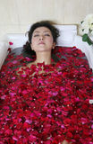 Rose petal spa. Young woman in rose petal water royalty free stock photos