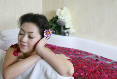 Rose petal spa. Young woman in rose petal water Stock Image