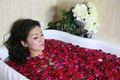 Rose petal spa. Young woman in rose petal water royalty free stock photography