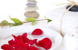 Rose Petal Spa With Rock Tower. Rose petals in water and spa items Stock Photography