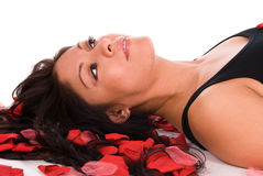 Rose petal woman. Beautiful Hispanic woman laying on her back with red rose petals scattered around her Stock Images