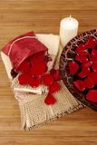 Rose Petals. Sachet of rose petals, luxurious towels, candle and Italian glass dish filled with red rose petals Stock Photo