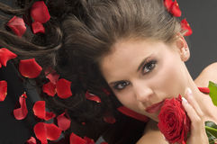 Rose and petals. Portrait of a young pretty woman with red rose and petals on hair royalty free stock image
