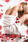 Rose petals. Young blond beauty in spa salon, over rose petals stock photography