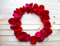 Rose Petals Border. On a wooden table royalty free stock photography