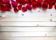 Rose Petals Border. On a wooden table royalty free stock image