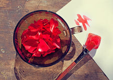 Rose petals in a bowl and a red paint Stock Photos