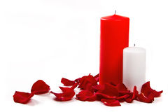 Rose petals and candles. The red rose petals with two candles royalty free stock photography