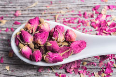 Rose petals and dried flowers in ceramic spoon Stock Photo