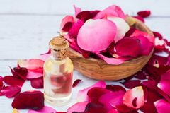 Rose petals and essential oil. Spa aromatherapy. Glass vial with rose essential oil and rose petals on Wooden bowl on a  white wooden background Royalty Free Stock Images