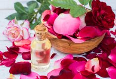 Rose petals and essential oil. Spa aromatherapy. Glass vial with rose essential oil and rose petals on Wooden bowl on a  white wooden background Royalty Free Stock Photos