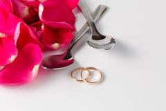 Rose petals and gold wedding rings Royalty Free Stock Photos