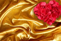 Rose petals on golden brown fabric silk. For background stock photography