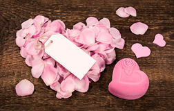 Rose petals in heart shape on wooden Royalty Free Stock Images