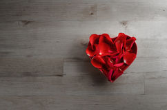 Rose Petals in Heart Shaped Bowl on Wood from Above Stock Photography