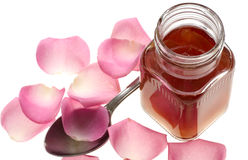 Rose petals jam. And spoon on white background stock images