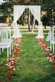 Rose petals laying on the green grass on the wedding ceremony. Wedding arch for the wedding ceremony, decorated with cloth and flowers on the green grass Royalty Free Stock Photo