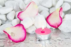 Rose petals and a lit candle for a spa decoration Royalty Free Stock Photos