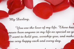 Rose petals and a  love letter. A romantic love letter with rose petals for Valentines day Stock Photo
