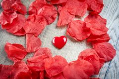 Rose petals and one heart on wood Valentine`s day. Rose petals and one heart on wood - Valentine`s day royalty free stock photo