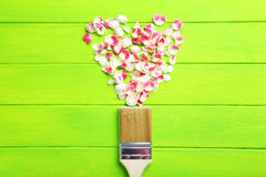 Rose petals. And paintbrush on green wooden table Stock Photography