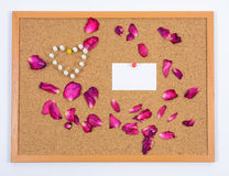 Rose petals, paper card and push pins on brown board Royalty Free Stock Image