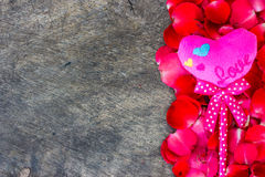 Rose Petals and pink heartson a wooden Royalty Free Stock Photos