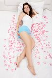 Rose petals surround a woman laying on a bed. Young brunette woman relaxing on a bed with white bed covers Royalty Free Stock Photos