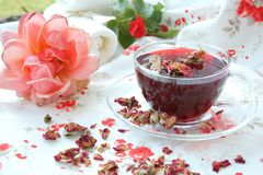 Rose petals tea. A glass cup of rose tea. Dehydrated rose petals and blossoms in the background royalty free stock images