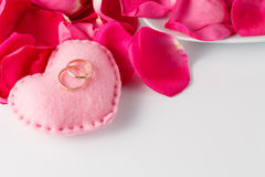 Rose petals and wedding rings Royalty Free Stock Photography