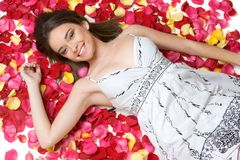 Rose Petals Woman. Beautiful woman laying in rose petals stock image