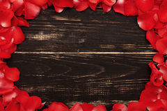 Rose petals on wooden vintage background Royalty Free Stock Photos