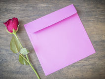 Rose and pink envelope. On wooden table royalty free stock images