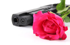 Rose and pistol. Red rose and black pistol on white background royalty free stock images