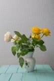 Rose a placé sur le bureau à l'arrière-plan bleu Photographie stock