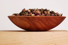 Rose Potpourri. Rose bud potpourri in a wooden bowl on a wooden shelf Stock Images