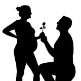Rose for a pregnant woman. Silhouette of a happy pregnant couple on a white background royalty free stock image