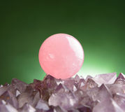 Rose quartz. Sphere of rose quartz natural crystal on amethyst rock Stock Photo