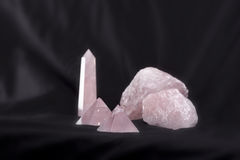 Rose Quartz Collection. Rose quartz stones: rough and carved. Pyramids, tower / wand, and chunks of raw material on a black background. The quartz facets appear Stock Photos
