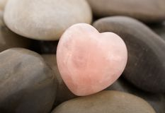 Rose quartz heart. On pebbles Stock Photos