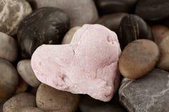 Rose quartz heart. Stone Composition - Rose quartz heart on pebbles background Stock Images