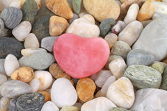 Rose quartz heart. Beautiful rose quartz gem heart on pebbles Royalty Free Stock Image