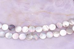Rose quartz texture with small mother pearl shells necklace ornament. Rose pink quartz gemstone surface background with round mother pearl ornament royalty free stock photography