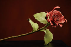 The rose with a red bloom and a green stalk made of metal. Stock Photo